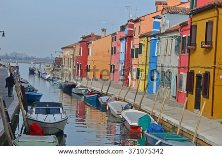 Canal leading into the Venice lagoon lined with boats and colourful houses, on the island of Burano, Italy - stock photo