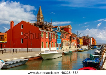 Canal with colorful houses, bridge and church on the famous island Burano, Venice, Italy - stock photo
