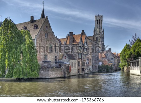 Canal with historical houses and the Belfort tower in Bruges, Belgium - stock photo