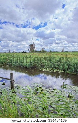 Canal with lilies and windmills on a cloudy, windy day at Kinderdijk, The Netherlands - stock photo