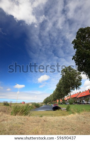 Canal with trees, houses and blue cloudy sky