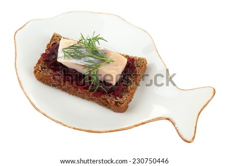 Canape herring with beets on rye toast on plate, isolated on white - stock photo