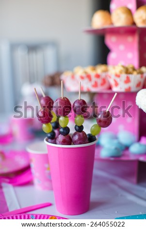 Canape of fruit, white chocolate cake pops and popcorn on sweet children's table at birthday party - stock photo