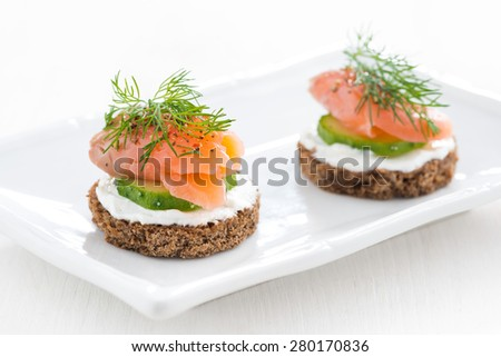 canape with cheese, cucumber and salted salmon on white plate, close-up - stock photo