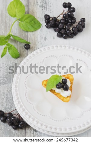 canape with cottage cheese and black berries of mountain ash in a plate and fresh mint leaves on a white wooden background. light sweet snack. healthy breakfast - stock photo