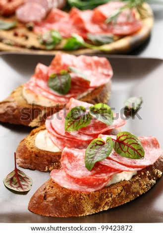 Canape with cream cheese, salami and herbs - stock photo