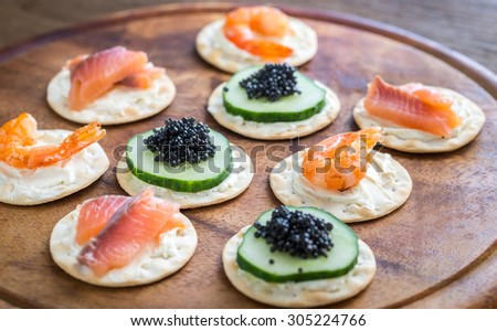 Canape with seafood on the wooden board - stock photo