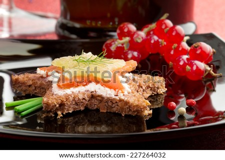 canape with smoked salmon and cream cheese on black dish - stock photo