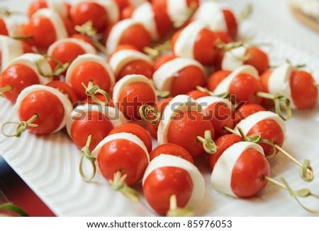 Canapes of  mozzarella cheese and cherry tomatos - stock photo