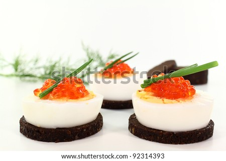 Canapes with boiled egg, chives and caviar - stock photo