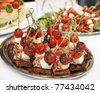 Canapes with choriso wurst on a metal platter - stock photo