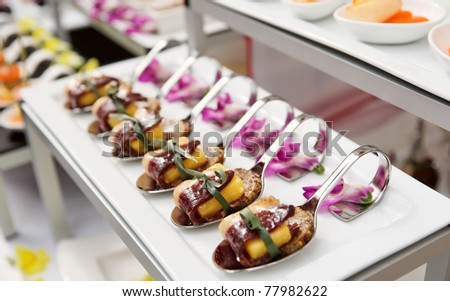 Canapes with cured ham (jamon or prosciutto) on banquet table, selective focus - stock photo