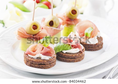 canapes with ham and olives - stock photo