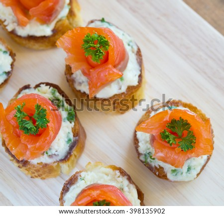 canapes with salmon and cheese on wooden board - stock photo