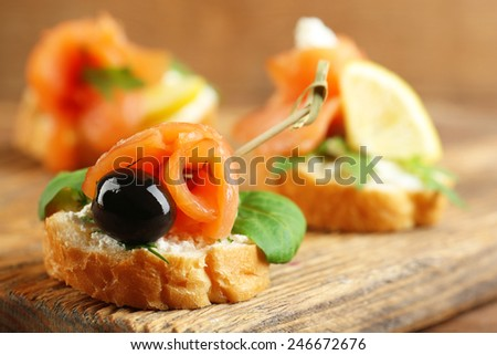 Canapes with salmon, black olive and herbs on cutting board, on wooden background - stock photo
