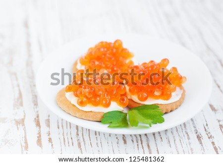 Canapes with  salmon red caviar on a white background