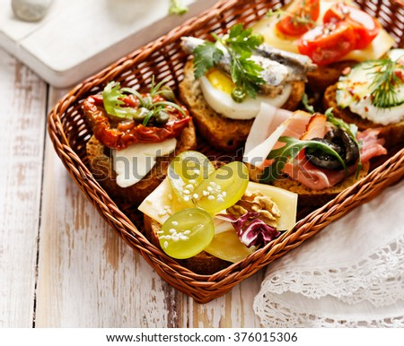 Canapes with various toppings, delicious breakfast or snack. Delicious slices of grilled baguette with various toppings  on rustic wooden table - stock photo