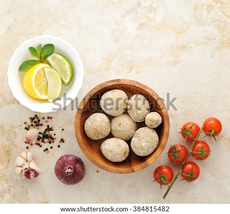 Canarian potatoes - boiled with salt, arugula, lime, lemon, tomato, garlic and spices on a marble background. Top view - stock photo
