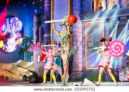 CANARY ISLAND, SPAIN - FEBRUARY 20, 2015: Drag Vulcano with costume from Isidro Javier Perez Mateo and unidentified assistants with lollipops onstage during Las Palmas carnival Drag Queen Gala. - stock photo