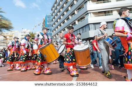CANARY ISLAND, SPAIN - FEBRUARY 17, 2015: Unidentified dummers with clown costumes from Murga Los Trapasones walking to samba rhythms in the streets during city of Las Palmas carnival in the sun. - stock photo