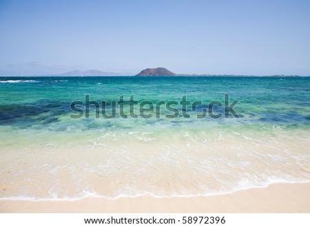Canary islands; white sand beach on Fuerteventura; small island Isla de Lobos and Lanzarote in the background; - stock photo
