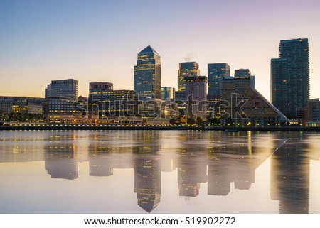 Canary Wharf business district with water reflection at sunset