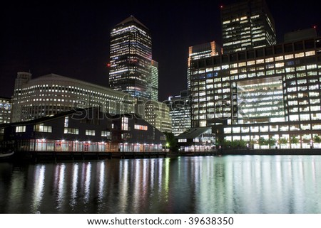 Canary Wharf skyscrapers in London at night with reflections in the river - stock photo