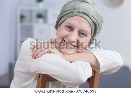 Cancer woman with headscarf sitting on chair, smiling - stock photo