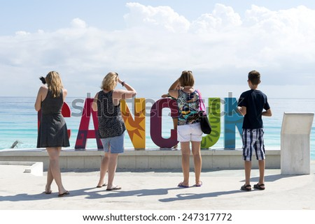 CANCUN - JANUARY 20: Tourists take pictures with the inscription CANCUN before the beach Playa Delfines on 20 January 2015 in Cancun, Mexico. This is one of the best beaches in the Mexico.