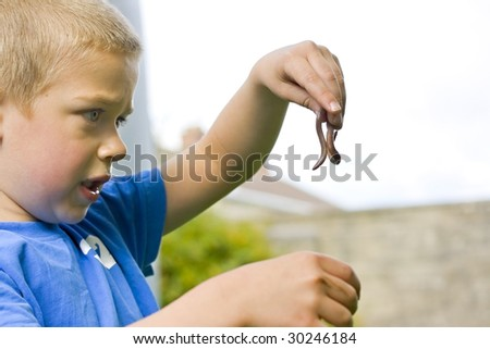 Candid close up portrait of a cute six year old boy playing with a worm