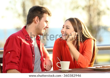 Candid couple date falling in love flirting in a terrace looking each other with tenderness thinking to kiss - stock photo