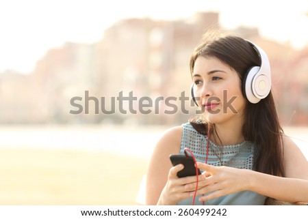 Candid girl thoughtful and listening to the music with a smart phone and looking away - stock photo