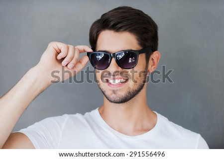 Candid handsome. Handsome young man adjusting eyewear and smiling while standing against grey background - stock photo