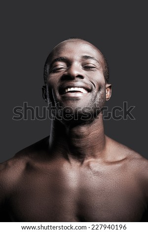 Candid happiness. Portrait of young shirtless African man keeping eyes closed and smiling while standing against grey background - stock photo