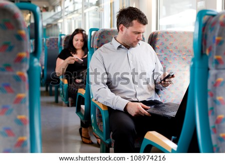 Candid image of a businessman working on a train - stock photo
