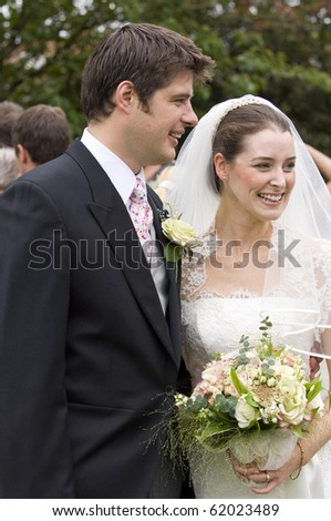 candid image of a happy bride and groom immediately after their wedding ceremony - stock photo