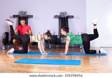 Candid image of a personal trainer working with his clients in a health club - stock photo