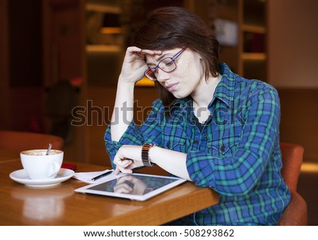 Candid image of a young woman using tablet computer in a cafe