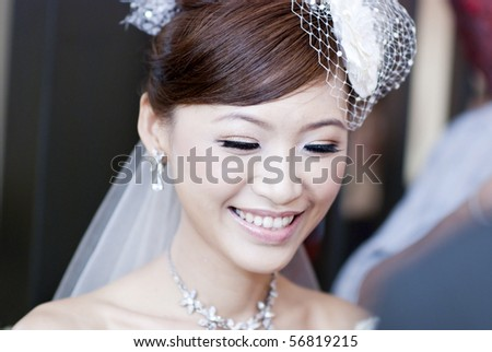 Candid moment of beautiful Asian bride smiling - stock photo