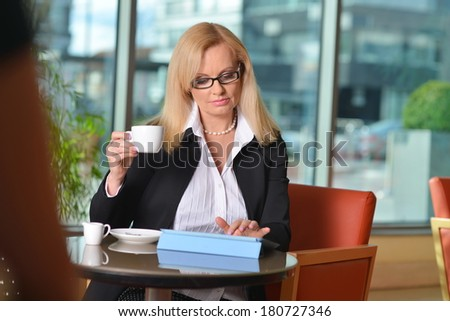 Candid photo of a attractive middle-aged blond businesswoman working at hotel lobby with a tablet pc/smartphone and drinking coffee  - stock photo
