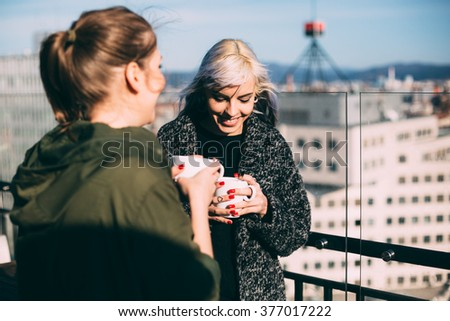 Candid photo of hip young women talking in roof top cafe