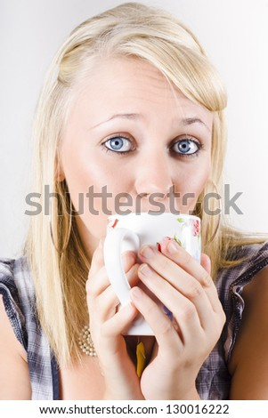 Candid portrait of a gorgeous blonde woman enjoying a hot drink