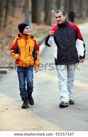 Candid portrait of father and son outdoor in the park - stock photo
