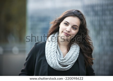 Candid portrait of young brunette woman looking away outside with copy space - stock photo