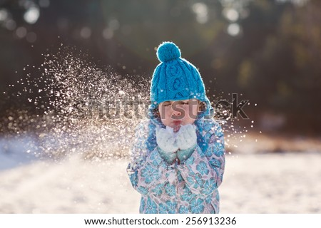 Candid shot of a cute little girl blowing snow flakes from her hands outdoors on a sunny winter's day - stock photo