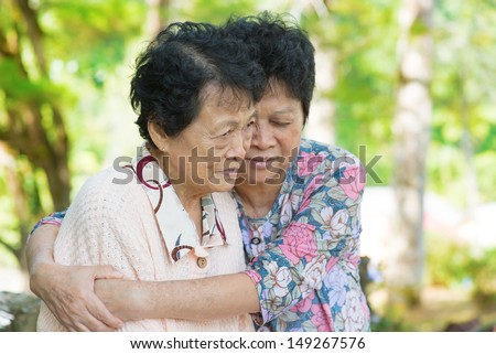 Candid shot of an Asian mature woman hugs and consoling her crying old mother at outdoor natural park.  - stock photo