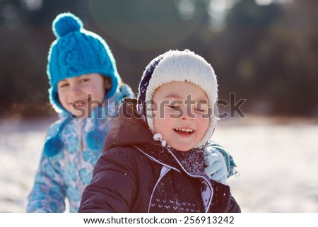 Candid shot of little boy and girl siblings outdoors on a sunny winter's day - stock photo