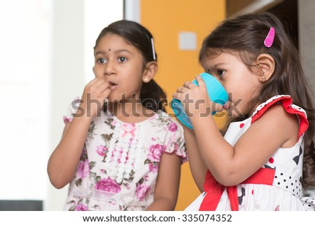 Candid shot of two cute Indian girls eating food and drinking water. Asian sibling or children enjoying tea time food, living lifestyle at home. - stock photo