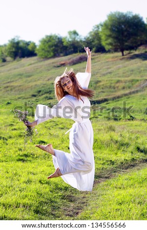 Candid skipping carefree adorable woman in field with flowers at summer sunset - stock photo