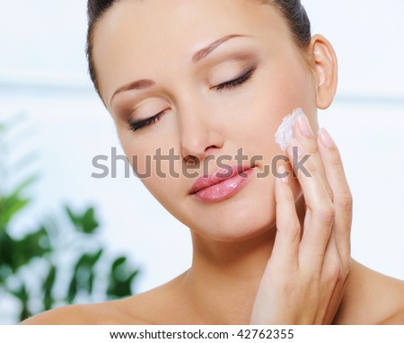 Candid woman face with closed eyes applying  moisturizer cream on her cheek - stock photo